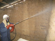 A spray operator applying insecticide to a wall surface